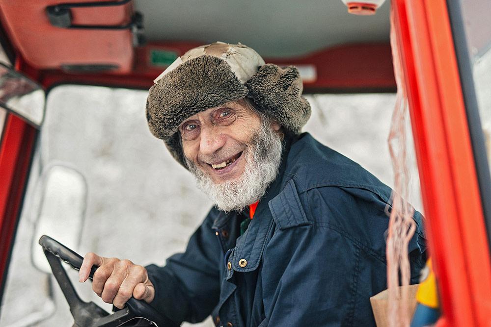 Rasimäen kylässä koko elämänsä asunut Matti Pursiainen ajaa traktorilla kyläilemään ystäviensä luona